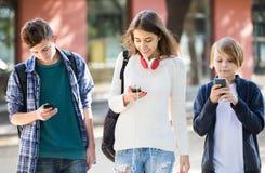 Tre tonåringar med smartphones i utomhus Royaltyfria Foton