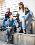 Tre tonåringar med telefoner utomhus Arkivbilder