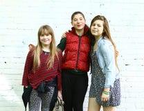 Tre tonåringflickor stänger sig upp den utomhus- ståenden royaltyfria foton