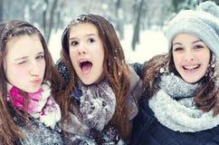 Tre tonårs- flickor som har gyckel i snön Royaltyfri Fotografi