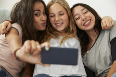 Tre tonårs- flickor som hemma tar selfie, fokus på flickor Royaltyfri Foto