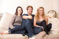 Tre tonårs- vänner som sitter hållande ögonen på television Arkivbilder