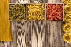 Tre träaskar med kulör fusilli är på en träbakgrund bredvid spagetti och tagliatelle fotografering för bildbyråer