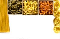 Tre träaskar med kulör fusilli är på en vit bakgrund bredvid spagetti och tagliatelle royaltyfri foto