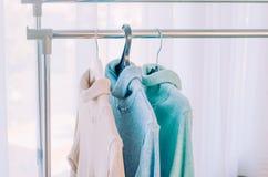 Tre tröjor av pastellfärgade skuggor på hängare fotografering för bildbyråer