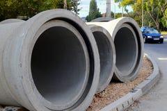 Tre tubi concreti si trovano sul marciapiede non finito vicino alla strada al sito degli impianti della costruzione di strade nel fotografie stock libere da diritti