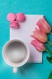 Tre tulipani rosa, una tazza di caffè e tre maccheroni rosa Fotografie Stock Libere da Diritti