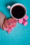 Tre tulipani rosa, una tazza di caffè e tre maccheroni rosa Immagine Stock Libera da Diritti