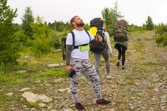 Tre turister med ryggsäckar arkivfoton