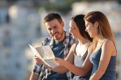 Tre turister som kontrollerar översikten i en stad arkivbild