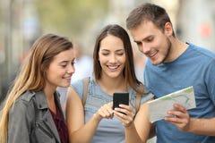 Tre turister som kontrollerar läge på gatan royaltyfri bild