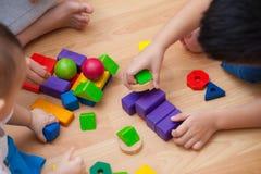 Tre unga barn som spelar med träkvarter i rummet Arkivbilder