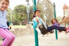 Tre unga flickor som spelar på gunga i lekplats Arkivbilder