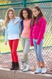 Tre unga flickor som ut hänger i, parkerar tillsammans Arkivfoton