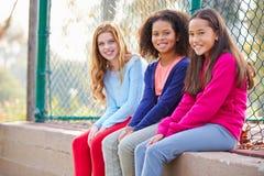 Tre unga flickor som ut hänger i, parkerar tillsammans Arkivbild