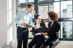 Tre unga gladlynta anställda som ler i ett modernt kontor royaltyfria bilder