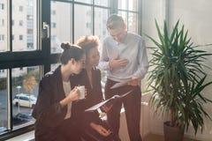 Tre unga gladlynta anställda som ler i ett modernt kontor royaltyfria foton
