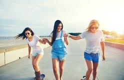 Tre unga gladlynta flickor som skateboarding i solljus royaltyfri bild