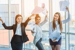 Tre unga härliga brunettaffärsdamer i kontoret All lycklig dansa dans upp dokumenten upp med royaltyfri bild