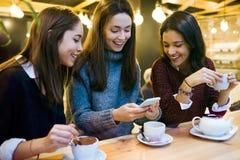 Tre unga härliga kvinnor som använder mobiltelefonen på kafét, shoppar fotografering för bildbyråer