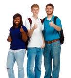 Tre unga högskolestudenter som visar tummarna, up tecknet Arkivfoton
