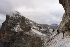 Tre unga klättrare på ett utsatt via Ferrata i dolomitesna Arkivbilder
