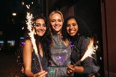 Tre unga kvinnliga vänner som tycker om helgdagsafton för nya år royaltyfri foto