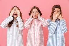 Tre unga kvinnor i hem- kläder som visar kloka symboler av trädet Fotografering för Bildbyråer