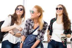 Tre unga kvinnor i solglasögon som står i flygplatsen och skrattet En tur med vänner Royaltyfri Bild