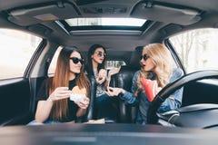 Tre unga kvinnor kör en bil som talar sig och äter en snabbmat i en bil i trafikstockning Royaltyfria Bilder