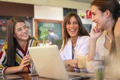 Tre unga kvinnor på kafét, skvaller och att le arkivfoton