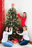Tre unga kvinnor som dekorerar en julgran Arkivfoton
