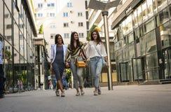 Tre unga kvinnor som går gatan som rymmer händer arkivfoton