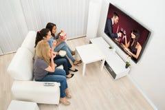 Tre unga kvinnor som håller ögonen på film royaltyfri bild