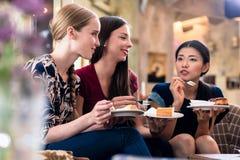 Tre unga kvinnor som inomhus äter kakan royaltyfria foton