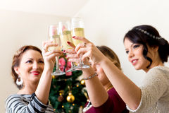 Tre unga kvinnor som rostar med champagne Fotografering för Bildbyråer