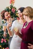Tre unga kvinnor som rostar med champagne Royaltyfri Bild