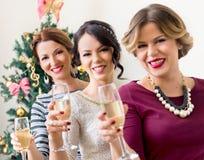 Tre unga kvinnor som rostar med champagne Arkivfoto