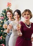 Tre unga kvinnor som rostar med champagne Arkivbilder