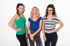 Tre unga kvinnor som står i studio Royaltyfria Foton