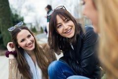 Tre unga kvinnor som talar och skrattar i gatan Royaltyfri Foto