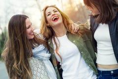 Tre unga kvinnor som talar och skrattar i gatan Arkivbild