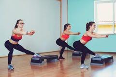 Tre unga kvinnor som tillsammans gör genomkörare i idrottshall Kondition- och livsstilbegrepp Royaltyfri Fotografi