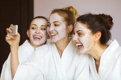 Tre unga lyckliga kvinnor med framsidamaskeringar på brunnsortsemesterorten Frenship Royaltyfria Foton