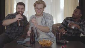 Tre unga lyckliga vänner som dricker öl och hemma talar tillsammans stock video