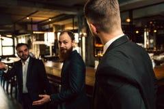Tre unga män i dräktlok på de Ett av dem ställning med baksida till kameran Kontorsarbetare står i bar fotografering för bildbyråer