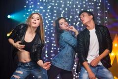 Tre unga män och två kvinnor har gyckel i en nattklubb arkivfoto