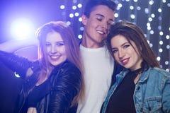 Tre unga män och två kvinnor har gyckel i en nattklubb royaltyfria bilder