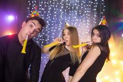 Tre unga män och två kvinnor har gyckel i en nattklubb royaltyfri foto