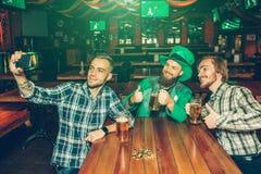 Tre unga män sitter på tabellen i bar och tar selfie De poserar på kamera och leende Grabb i mellersta hålltelefon royaltyfri fotografi